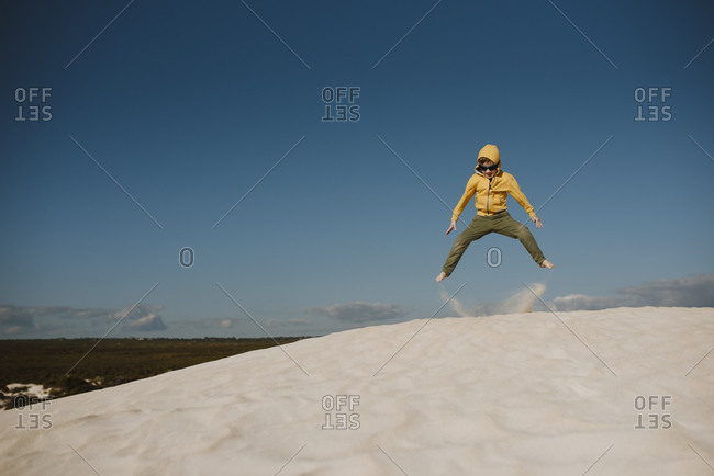 Boy jumping at the top of a sand dune