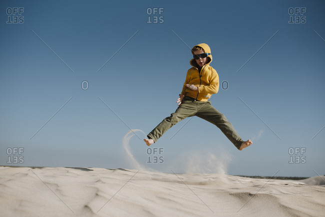Boy jumping on a sand dune