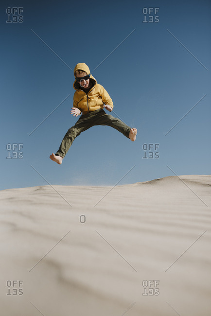 Young boy jumping on a sand dune