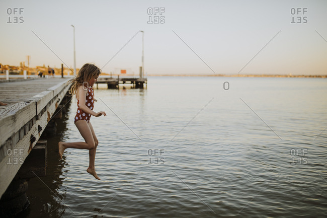 Girl jumping off the jetty into the river