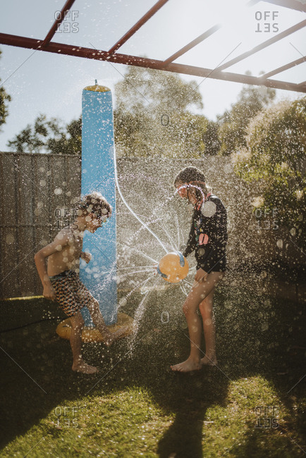 Children playing with water ball sprinkler in back yard