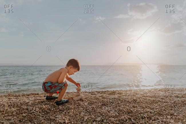 Child playing with stones on beach on his own at sunset. Young boy wearing summer shorts stacking pebbles on beach in the evening.