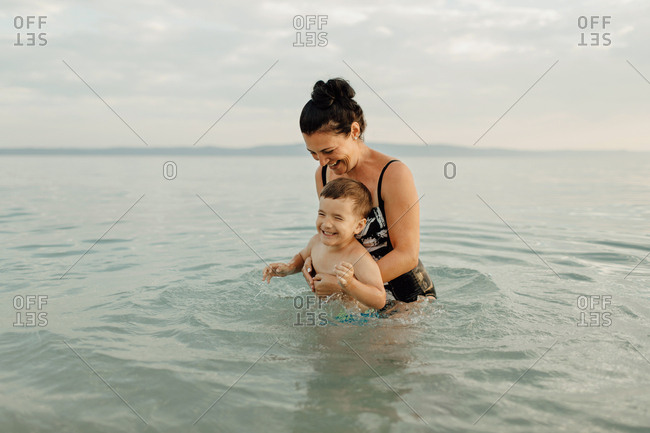 Mother and child playing in sea. Cheerful woman having fun with her toddler boy in water on hot summer day.