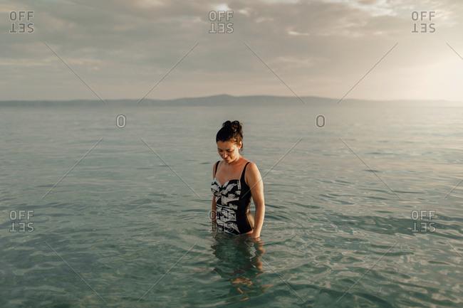 Woman standing in sea. Woman wearing swimwear standing still in water.