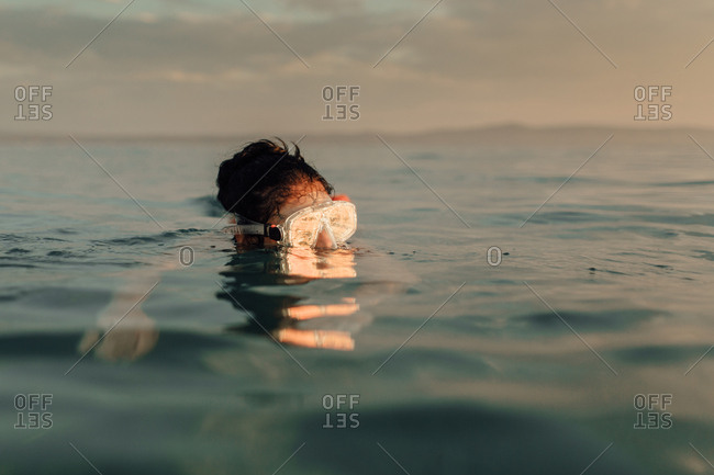 Woman swimming in sea at sunset. Snorkeling - woman wearing diving mask  watching sun go down.