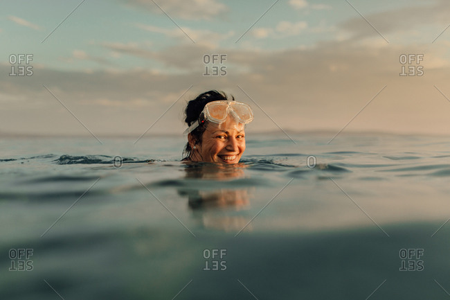 Woman swimming alone in sea at sunset. Woman wearing diving mask at top of head enjoying swimming in ocean in evening.