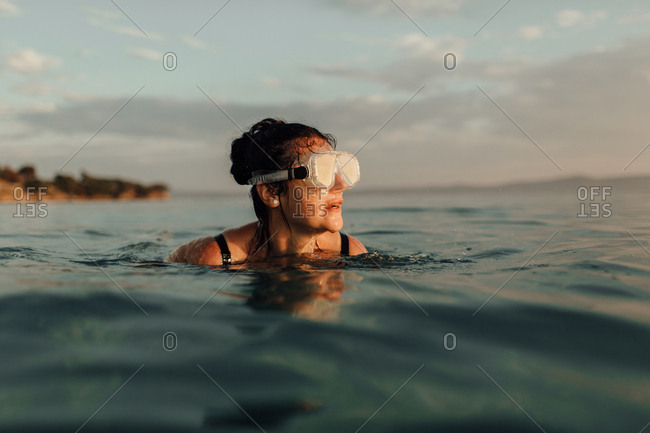 Woman swimming alone in sea at sunset. Woman wearing diving mask watching sun go down.