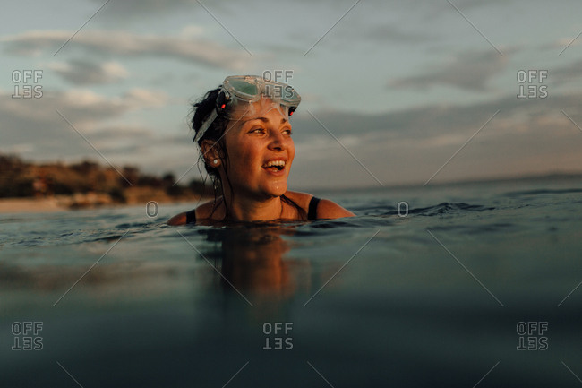 Woman swimming alone in sea at sunset. Woman with diving mask at the top of head watching sun go down.