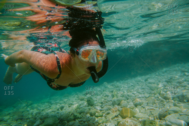 Woman snorkeling. Female diver wearing diving mask and snorkel swimming in shallow sea.
