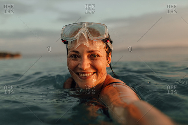Woman taking selfie in sea at sunset. Smiling woman wearing diving mask at top of head looking into camera swimming in ocean in the evening.