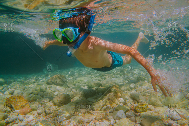 Child snorkeling. Young boy wearing diving mask and snorkel learning to snorkel in shallow sea.