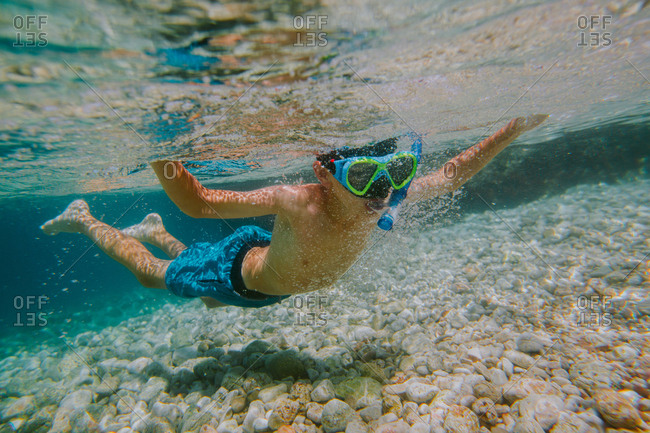 Child snorkeling. Young boy wearing diving mask and snorkel floating in shallow sea arms spread wide.