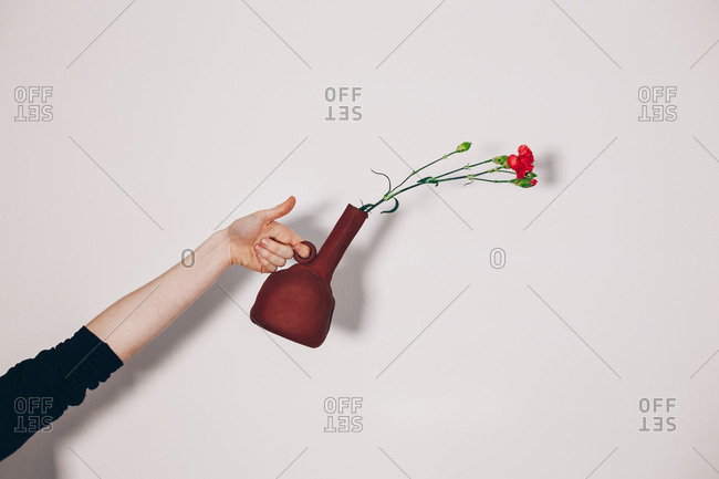 Close up of a ceramist hand holding a self-made red ceramic vase with a flower, in front of a white wall background. Authentic flowerpot artwork.