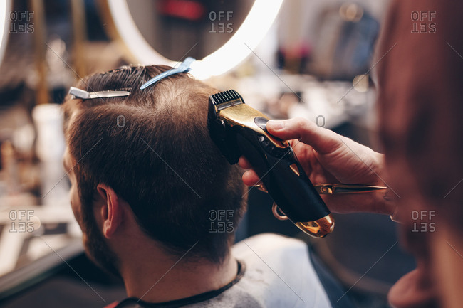 Close up shot of man getting trendy haircut at barber shop. Male hairstylist shaving and trimming clients hair using an electric trimmer.