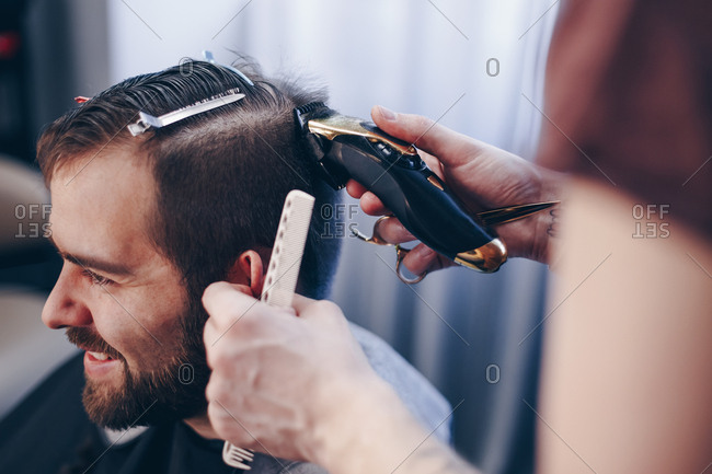 Young handsome man getting trendy haircut at barber shop. Male hairstylist shaving and trimming clients hair using an electric trimmer and comb.