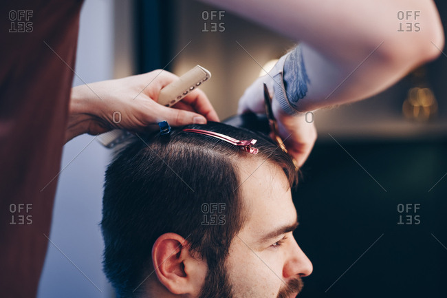 Side view of man getting modern haircut at barber shop. Male hairstylist shaving and trimming clients hair using an electric trimmer.