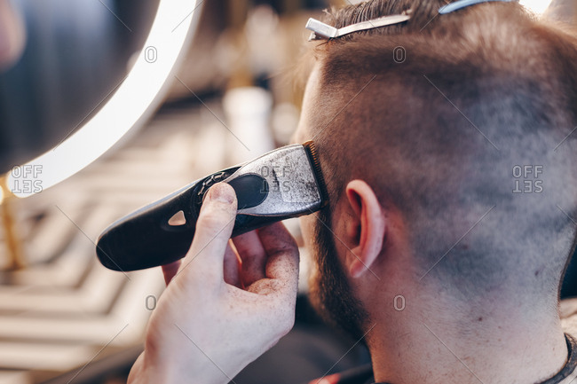 Male hairstylist shaving clients hair using an electric trimmer.  Back of the head view of  young man getting new haircut at barber shop.
