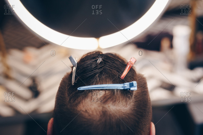 Detail shot of male client in a barbershop. Wet hair divided into sections and held with clippers.