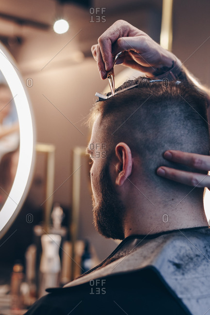 Rear view of attractive hipster man getting trendy haircut at barber shop. Hairstylist trimming clients hair using comb.