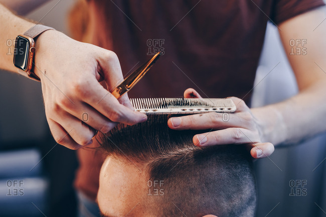 Hipster man getting trendy new haircut at barber shop. Hairdresser sectioning and trimming clients hair using comb and scissors.