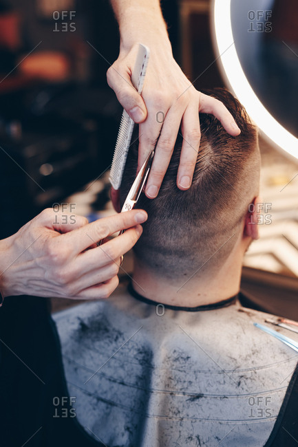 Top view of male hairdresseser giving client a new haircut, cutting hair using professional scissors.