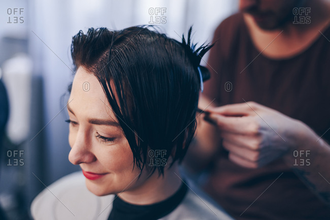 Close up of beautiful short haired young woman getting a new haircut at a beauty salon.