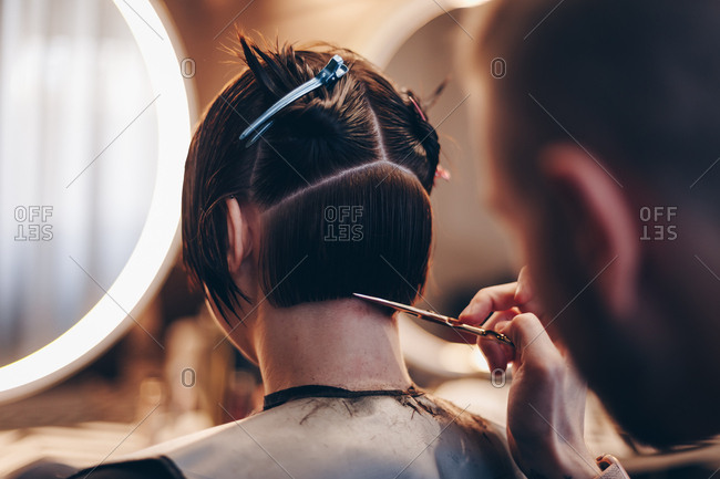 Detail shot of hairdresser sectioning and trimming clients hair using comb and scissors. Woman getting trendy haircut at beauty salon.