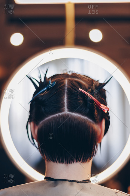 Rear view of female client in a beauty salon. Wet hair divided into sections and held with clippers.