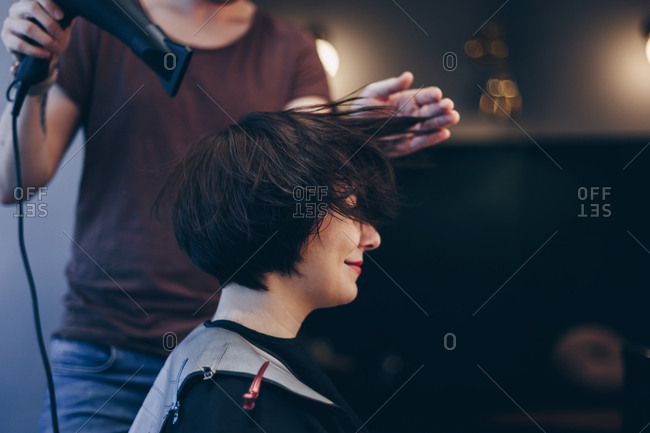 Beautiful young woman getting a new haircut at a salon. Male hairdresses blow drying clients hair.
