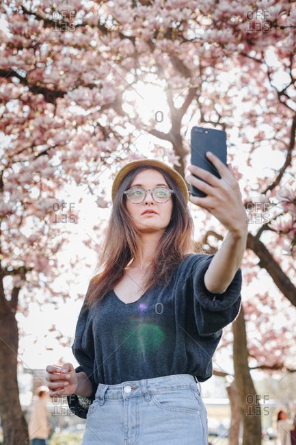 Candid portrait of stylish young woman taking a selfie with mobile phone, posing for social media in a park outdoors.