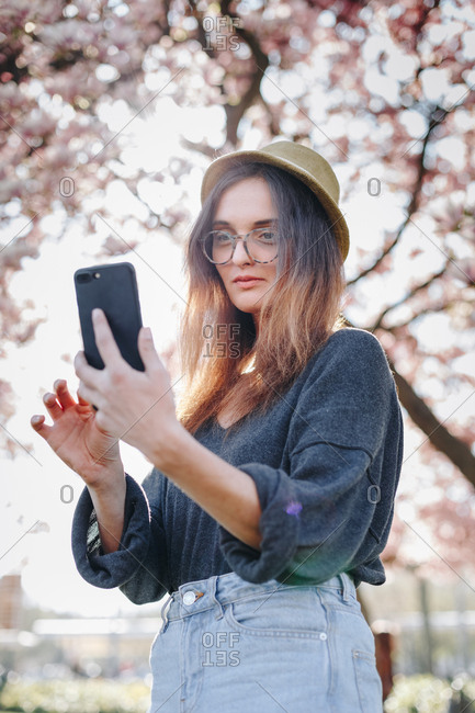 Authentic portrait of stylish young woman taking a selfie with mobile phone, posing for social media in a park outdoors, next to a magnolia tree in full bloom.