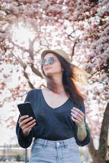 Authentic portrait of fashionable young tourist woman taking a selfie with mobile phone, posing for social media in a park outdoors on  a sunny spring day