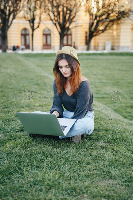 Portrait of young college student sitting on grass in park on a sunny day, using laptop to study for upcoming exams