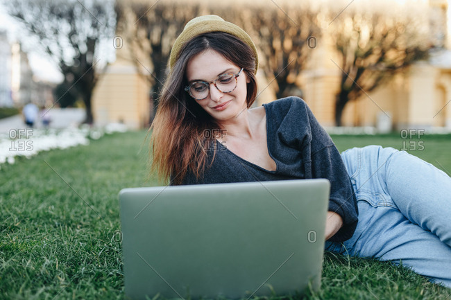 Authentic portrait of happy young freelancer woman sitting in park and using laptop to surf the internet and check for job opportunities.