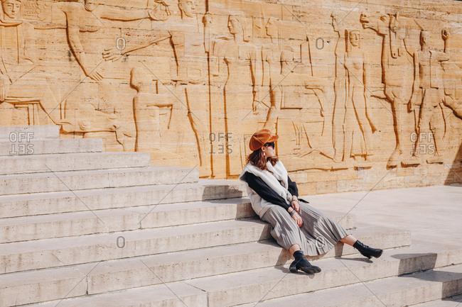 Ankara, Turkey - March 3, 2019:  Fashionable woman tourist posing for fashion blog photos at the Ataturk Mausoleum - An?tkabir on a sunny day