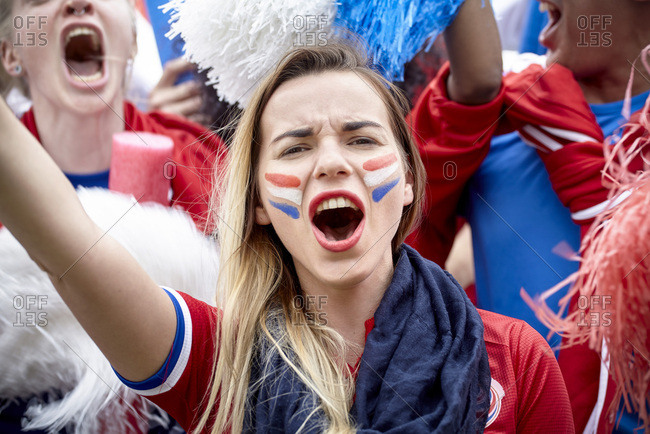 French football fan cheering at match, portrait