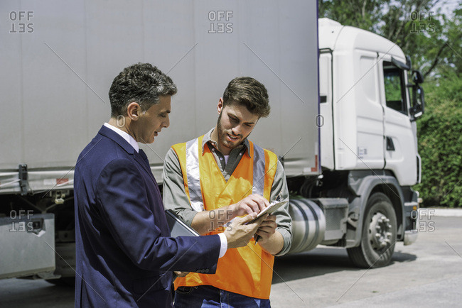 Worker and businessman discussing near lorry