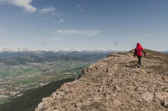 Young woman walking at the edge of a mountain