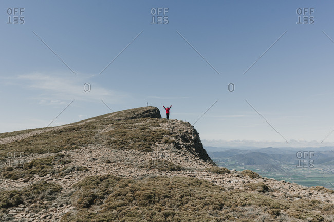 Young woman standing with hands up at the edge of a mountain