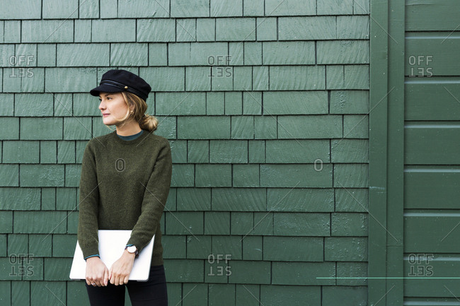 Portrait of young woman in front of green wall