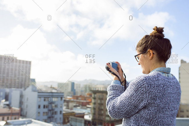 Young woman photographing city