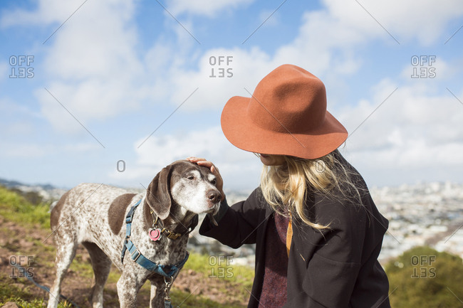 Young woman stroking dog