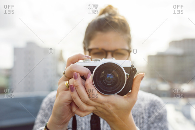 Young woman holding camera - Offset