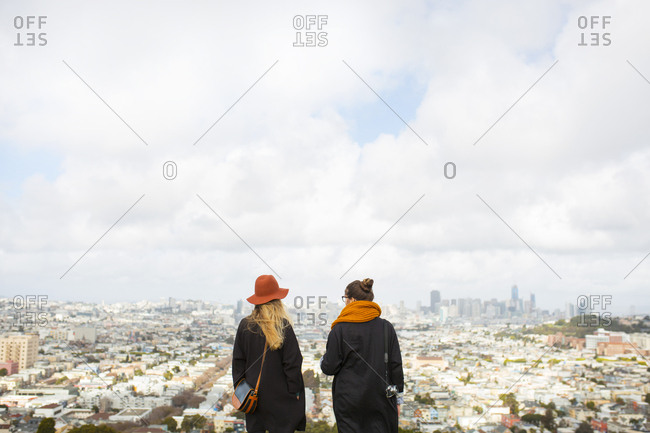 Rear view of two women looking at city