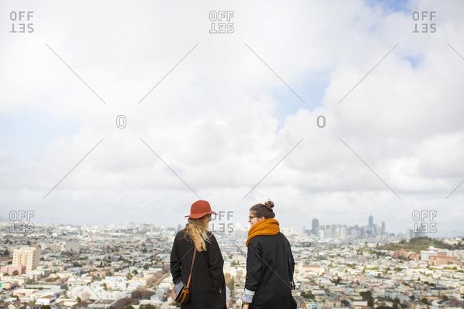 Rear view of two women standing in front of cityscape