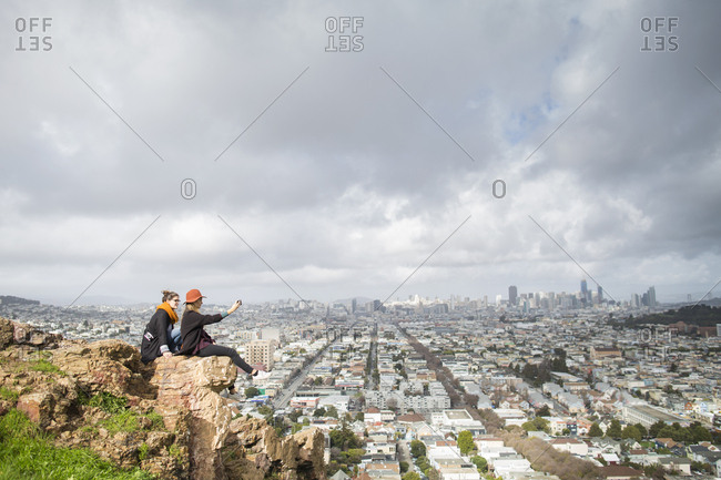Two young women sitting on cliff in front of cityscape