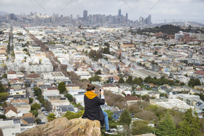 Young woman sitting on cliff and photographing city