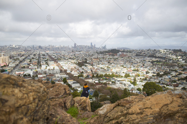 Young woman sitting on cliff in front of cityscape