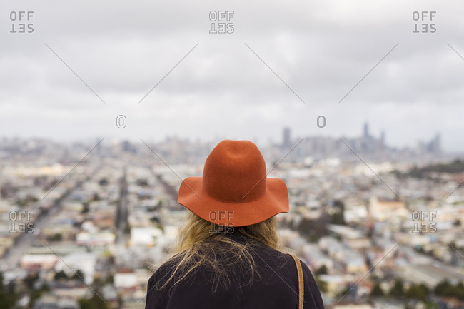 Rear view of woman wearing red hat in front of cityscape
