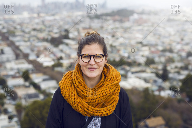 Portrait of young woman wearing orange scarf in front of cityscape